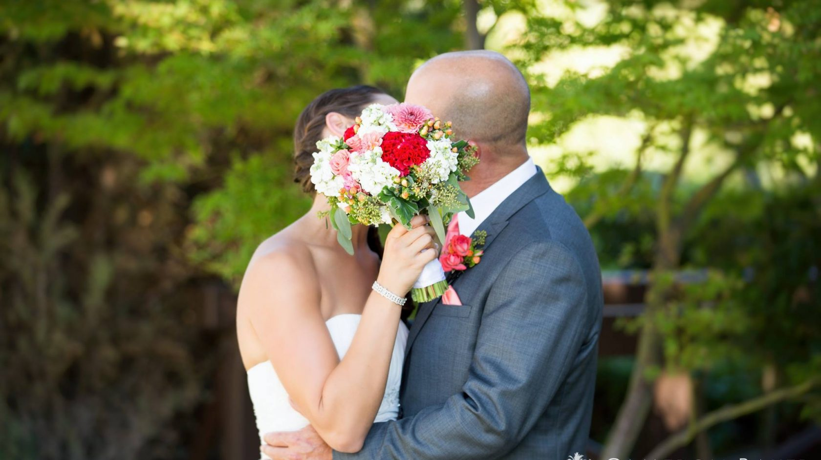 Newlyweds share a kiss behind the bouquet